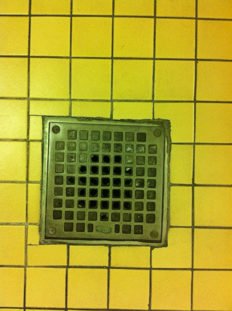 Right Past Down the Drain © 2012 NATE METZ - digital photograph of yellow tile and floor drain in a bathroom